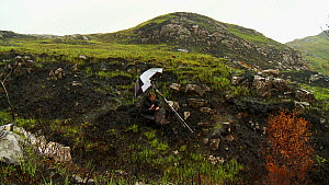 Joe Cornish photographing a fire-damaged landscape in the rain whilst on assignment for 2020vision, near Lochinver, Coigach / Assynt Scottish Wildlife Trust, Sutherland, Highlands, Scotland, UK, June...  -  Raymond  Besant / 2020VISION