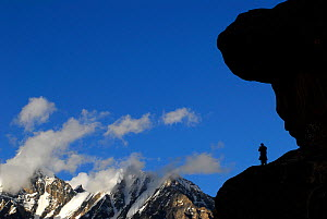 A Balti porter silhouetted standing on a rock, with mountains in the distance, Urdukas Camp (4,000m), Baltoro Glacier, Central Karakoram National Park, Pakistan, July 2007. - Enrique Lopez-Tapia