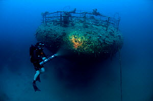 Wreck of the cargo ship 'Iouna'. Diver and ships stern with navigation light still attached on rail. Wrecked between 1912-1918. Sharmo reef, Yanbu, Saudi Arabia, July 2010  -  Michael Pitts