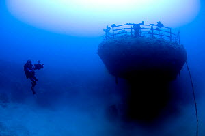 Wreck of the cargo ship 'Iouna'. Cameraman and ships stern with navigation light still attached on rail. Wrecked between 1912-1918. Sharmo reef, Yanbu, Saudi Arabia, July 2010  -  Michael Pitts