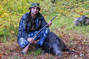 Young Romanian hunter posing with his first Wild boar (Sus scrofa) that he shot during a driving hunt in the forest area outside the village of Mehadia, Caras Severin, Romania, October 2012  -  Wild Wonders of Europe / Möllers