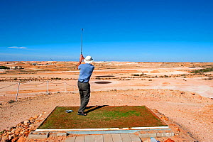 Man playing golf in deserrt at Coober Pedy, an outback desert, opal mining town, South Australia  -  Steven David Miller
