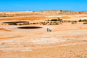 Man playing golf on course at Coober Pedy, an outback desert, opal mining town, South Australia, June 2010  -  Steven David Miller