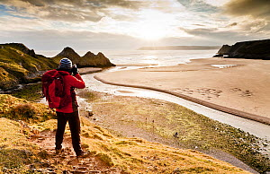 Man taking a photograph of Three Cliffs Bay, Gower, Swansea, Wales. January 2013. Model released.  -  Merryn  Thomas