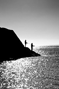 Two men fishing, Lansallos Cove, Cornwall, England, October 2012. Model released.  -  Merryn  Thomas