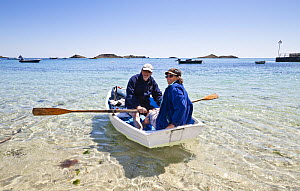 Man and woman rowing a skiff / punt, Par Beach, St. Martin's, Isles of Scilly, Cornwall, England, UK, May 2012. Model released. - Merryn Thomas