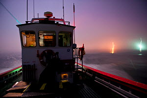 West coast rock lobster (Jasus lalandii) fishing boat (James Archer) leaves the Saldhana Bay harbour before the break of dawn. The lights of the town and the lighthouse flash on the horizon. Saldhana... - Cheryl-Samantha  Owen
