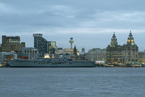 HMS Illustrious (Pennant Number R06) at dusk alongside the Liverpool Cruise Liner Terminal with the Royal Liver Buildings (right of image) in the background, Liverpool, Merseyside, United Kingdom, Feb... - Graham  Brazendale