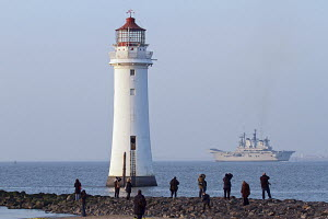 HMS Illustrious departs Liverpool, past New Brighton's Perch Rock Lighthouse, Liverpool, Merseyside, United Kingdom, February 2013. All non editorial uses must be cleared individually.. - Graham  Brazendale