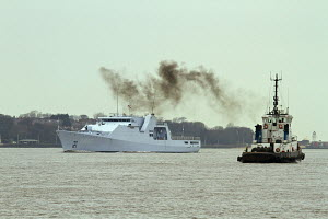 HNLMS Groningen (P843), a Royal Dutch Navy Holland-class Offshore Patrol Vessel, arrives in Liverpool, with tugboat emitting smoke, River Mersey, Liverpool, Merseyside, United Kingdom, March 2013. All... - Graham  Brazendale