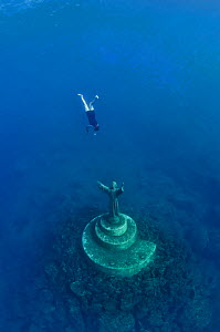 A fisherman swims down to touch the statue of Christ Of The Abyss (Cristo degli abissi) for good fortune, in the Marine Protected Area of Portofino (Area Marina Protetta, Portofino), Liguria, Italy. M...  -  Alex  Mustard
