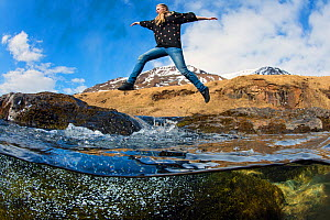 Girl leaps between stepping stones across a mountain river. Akureyri, Iceland. May 2011.  -  Alex  Mustard