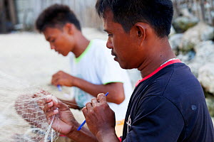 Men repairing nylon fishing nets, Batasan Island, Danajon Bank, Central Visayas, Philippines, April 2013  -  Claudio Contreras