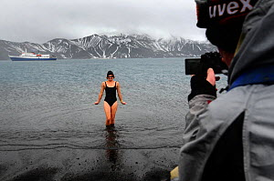 A tourist coming out of the water after a swim in hot springs, Deception Island, with Antarctic cruise liner 'MV Ushuaia' in the background. Antarctica.  -  Enrique Lopez-Tapia