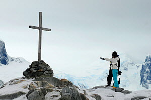 Tourists observing a memorial cross in honour of British Antarctic Survey crew, Ambrose C Morgan, Kevin P Ockleton and John Coll who died in 14 Aug 1982. Petermann Island. Antarctic peninsula, Antarct...  -  Enrique Lopez-Tapia