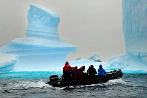 Tourists on a zodiac going past icebergs in Iceberg Alley, Pleneau Island, Antarctica  -  Enrique Lopez-Tapia