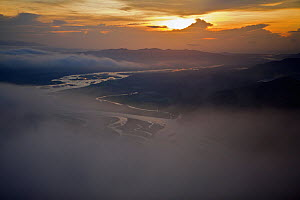 Aerial view of sunrise, low clouds and the Sarawaget Range - mountains of the Huon Peninsula, Papua New Guinea  -  Tim Laman/Nat Geo Image Collection
