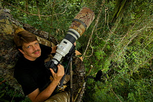 Photographer Tim Laman with camera set up on canopy platform to shoot King Bird of Paradise. Oransbari, Bird's Head Peninsula, New Guinea. August 2009  -  Tim Laman