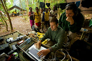 Eric Liner reviews footage on his laptop, while Edwin Scholes and villagers look on. West Papua, New Guinea, August 2009  -  Tim Laman