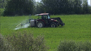 Wide shot of a tractor spraying pesticide or fertiliser on a field, France, April.  -  Ammonite
