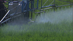 Close-up of a tractor spraying pesticide or fertiliser on a field, France, April.  -  Ammonite