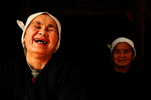 Two Dong women, one laughing, in a dark room, Sanjiang Dong Village in the province of Guangxi, China. April 2009. Winner of the Photographer of the Year, Portrait Category, 4th Pollux Awards, 2012 - Enrique López-Tapia