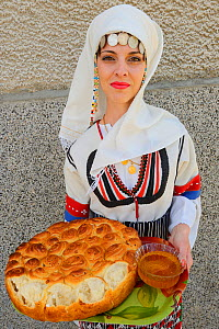Young woman in Balkan dress offering bread and honey at the celebration of the opening of a new Tahini-production factory in Kondovo village, Eastern Rhodope Mountains, Bulgaria, May 2013.  -  Wild  Wonders of Europe / Widstr