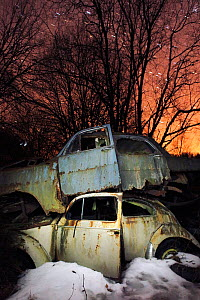 Old abandoned cars stacked on atop the other in 'car graveyard' at night, Bastnas, Sweden April  -  Pal  Hermansen