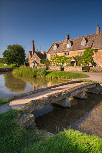 Stone footbridge and cottages in the picturesque Cotswolds village of Lower Slaughter, Gloucestershire, England. September 2012.  -  Adam  Burton