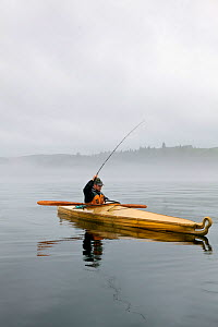 Man in kayak fishing with his home made bamboo fly rod on a foggy morning in the Strait of Juan de Fuca, Washington, USA, August 2013. - Kirkendall-Spring
