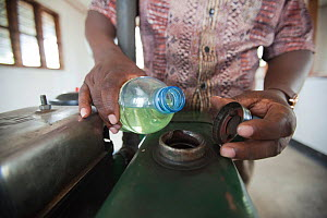 Man pouring Jatropha biofuel from a bottle to fuel a milling machine, Tanzania.  -  Tom  Gilks