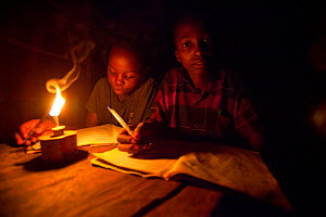 Tanzanian boys doing homework using oil lamp, Tanzania.  -  Tom  Gilks