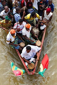 Villagers travelling in dugout canoe frome on village to another for traditional voodoo / vodun ceremony, Benin, February 2011. - Christophe Courteau