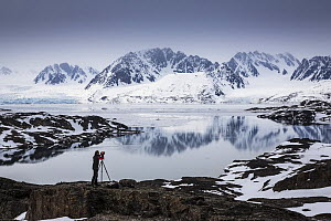 Landscape photographer taking a picture of the view across the Liefdefjorden, towards the Monacobreen Glacier, Spitzbergen, Svalbard, Norway, June, 2012. Model released. - Christophe Courteau