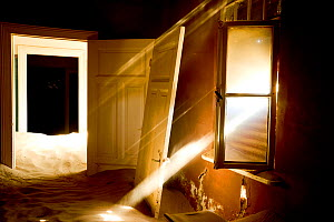 Light streaming through window on sand covered house in Kolmanskop Ghost Town, an old diamond-mining town where shifting sand dunes have encroached abandoned houses, Namib Desert Namibia, October 2013... - Enrique Lopez-Tapia