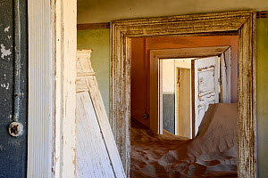 Abandoned house full of sand. Kolmanskop Ghost Town, an old diamond-mining town where shifting sand dunes have encroached abandoned houses, Namib Desert Namibia, October 2013.  -  Enrique Lopez-Tapia