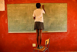 Girl writing on blackboard in rural school in the region of Kaokoland, Namibia, February 2005.  -  Enrique Lopez-Tapia