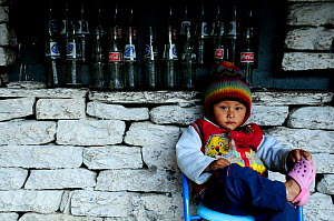 A child sitting by wall with empty glass bottles, in the small village of Khumnu. Annapurna Sanctuary, central Nepal, November 2011. - Enrique Lopez-Tapia