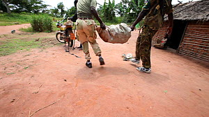 Ecoguards putting  a sack of bushmeat onto a motorbike after an inspection, Bayanga village, Dzanga-Ndoki National Park, Sangha-Mbaere Prefecture, Central African Republic, May 2012. - Jabruson Motion