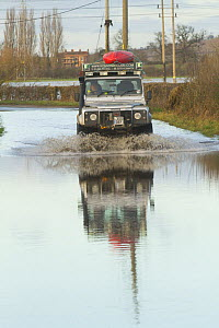 Landrover with kayak driving through water during the February 2014 floods, Gloucestershire, England, UK, 7th February 2014.  -  David  Woodfall