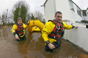 Rescue workers entering property with inflatable raft to check on home owners,  during February 2014 flooding, Upton upon Severn, Worcestershire, England, UK, 9th February 2014.  -  David  Woodfall