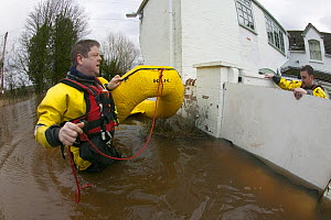 Rescue workers entering property from safety of  lightweight boat to check property for its safety and rescue homeowners in February 2014 flood of properties by River Severn.  -  David  Woodfall