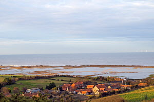 View over flooded grazing marsh and breached shingle coastal defense after the 6th December east coast tidal surge, with the village of Salthouse in the foreground, Norfolk, England, UK, December 2013... - Gary  K. Smith