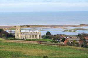 View towards St Nicholas Church, with flooded grazing marsh and breached shingle coastal defense after the 6 December east coast tidal surge in the background, Salthouse, Norfolk, England, UK, Decembe...  -  Gary  K. Smith