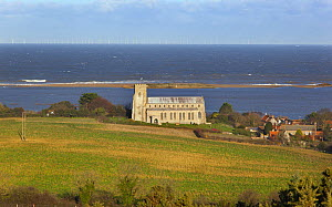 View towards St Nicholas Church, with flooded grazing marsh and breached shingle coastal defense after the 6th December east coast tidal surge in the background, Salthouse, Norfolk, England, UK, Decem... - Ernie  Janes
