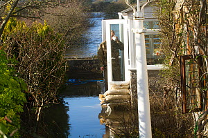 Man standing in doorway of flooded home during January 2014 flooding, Somerset Levels near Langport, Somerset, England, UK, 11th January 2014. - David  Woodfall