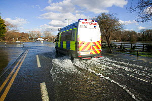 Police van driving through February 2014 floods. Chertsey, Surrey, England, UK, 16th February 2014. - David  Woodfall
