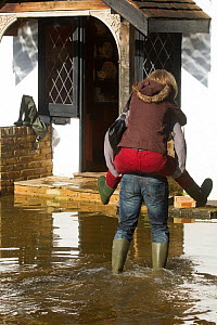 Resident giving a piggy back ride outside flooded home during February 2014 flood. Surrey, England, UK, 16th February 2014.  -  David  Woodfall