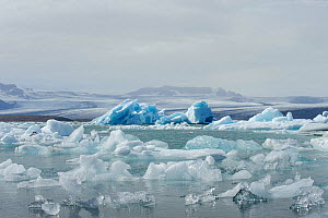 Vatnajokull Glacier with ice floating on Jokulsarlon glacial lake, Iceland, July 2012.  -  Terry  Whittaker