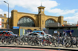 Bicycles attached to bike racks in front of taxis and traffic with King's Cross Station behind, London, England, UK, July 2013.  -  Pat  Tuson